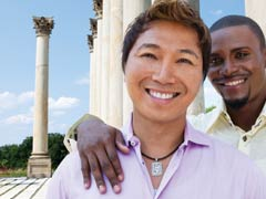Two smiling men on a travel adventure posing in front of a monument