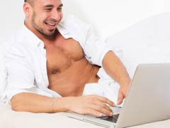 Attractive man chatting online with other gay men on webcam